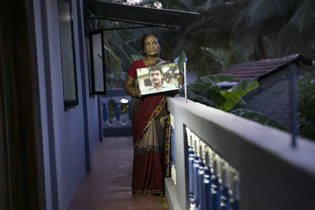 Lelladevi Anadanadarajah holds a photo of son, Anuraj  Anadanadarajah in Kilinochchi, Sri Lanka. Lelladevi Anadanadarajahs son, Anuraj  Anadanadarajah, has been missing since May 15, 2009. He was passing a police checkpoint on the road and was taken into custody, and she has not heard from him since. Anuraj's wife was 7 months pregnant at the time with their second child. Lelladevi has filed complaints with several agencies and met the Sri Lankan president, but hasn't heard news. {quote}We want justice for our kids. There are still so many in detention camps. They're using them as slaves, they're working them and torturing them to death. This is my fear. Only the international community can help us now. There are kids who were so small when their parents were taken, they're growing up now without their moms or dads and they may want to take revenge and join these groups. They have to release these people or give us the truth. They have to give us justice.{quote}