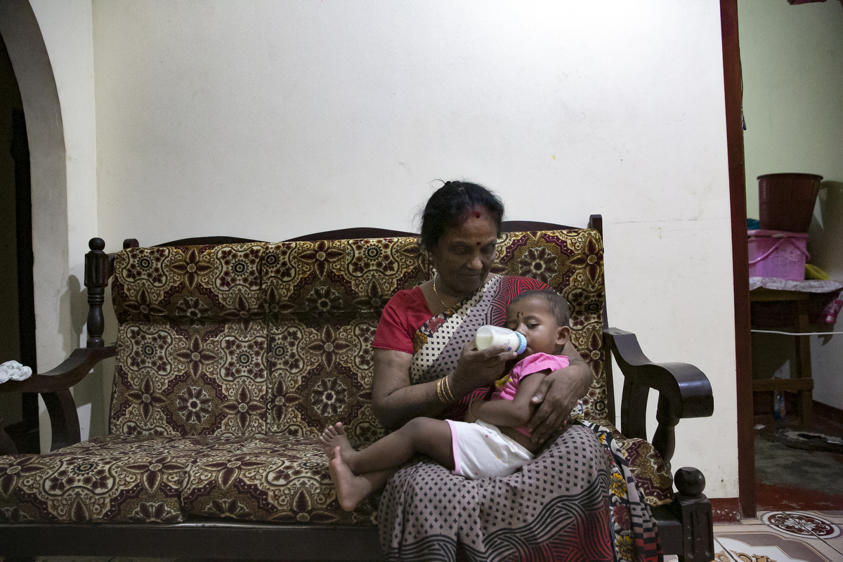 Lelladevi Anadanadarajah cares for one of her grandchildren in Kilinochchi, Sri Lanka. Lelladevi Anadanadarajahs son, Anuraj Anadanadarajah, has been missing since May 15, 2009. He was passing a police checkpoint on the road and was taken into custody, and she has not heard from him since. Anuraj's wife was 7 months pregnant at the time with their second child. Lelladevi has filed complaints with several agencies and met the Sri Lankan president, but hasn't heard news. {quote}We want justice for our kids. There are still so many in detention camps. They're using them as slaves, they're working them and torturing them to death. This is my fear. Only the international community can help us now. There are kids who were so small when their parents were taken, they're growing up now without their moms or dads and they may want to take revenge and join these groups. They have to release these people or give us the truth. They have to give us justice.{quote}