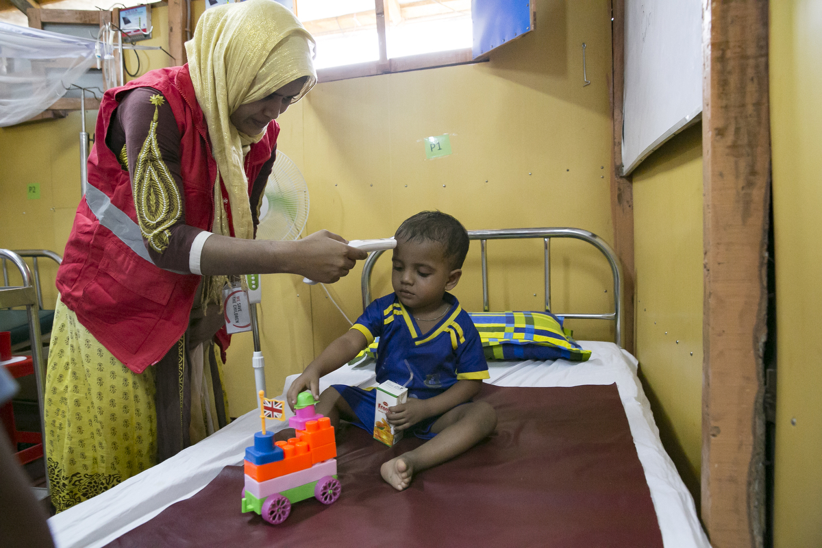Anwar plays during a checkup at the PHCC October 1, 2018 in the Rohingya refugee camp in Cox's Bazar, Bangladesh. Anwar (22 months) is a Rohingya refugee who lives with his mother Rahima and father Mohammed Amin, brother and sister in the Rohingya refugee camps in Cox's Bazar, Bangladesh. In June 2018, Anwar was admitted to the Save the Children Primary Health Care Centre (PHCC) suffering from symptoms of pneumonia. After three days of treatment, where he received care from Save the Children's doctors and paramedics, Anwar was discharged from the PHCC. Rahima and Mohammed said that in Myanmar it would take a whole day to get to a hospital, so they didn't go very often. They are now happy and feel good that they have a good health care centre located close to their home in the camps. They said they want to think Save the Children for all their help, and that if they return to Myanmar they will never forget the help they have received from Save the Children. They said that they would recommend all their friends and neighbours to come to the PHCC because the treatment is good, and there are doctors and nurses.
