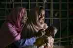 Rohana Begum is seen with her baby Khotija and mother Sufaida Begum September 30, 2018 in the Rohingya refugee camp in Cox's Bazar, Bangladesh. Rohana was brought to the PHCC when she started hemorrhaging immediately after childbirth. When she was stabilised, the PHCC team put her in an ambulance and took her to a hospital, where she received emergency treatment. She made a full recovery. Now, Rohana and Khotija are doing well. They have been back to the PHCC several times for checkups, and Rohana is very happy with the care they have received. Rohana thinks she would have died if it had not been for Save the Children. They now tell other Rohingya women to give birth in the maternity ward at the PHCC, because it is safe and they can receive emergency treatment if needed.