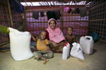 Sufaida Begum poses for a photo with her children Mohammed Hassen (right) and Shahanj (left) with food donated by Save The Children October 4, 2018 in the Rohingya refugee camp in Cox's Bazar, Bangladesh.