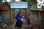 Sonzida (blue hijab) and Tosnim (red hijab) gather water to bring to a Women Friendly Space in a Rohingya refugee camp June 29, 2018 in Cox's Bazar, Bangladesh. Allison Joyce/UNFPA