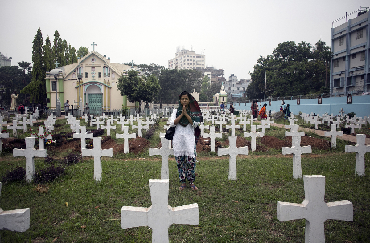 A woman prays a graveyard at a Christian church in Bangladesh