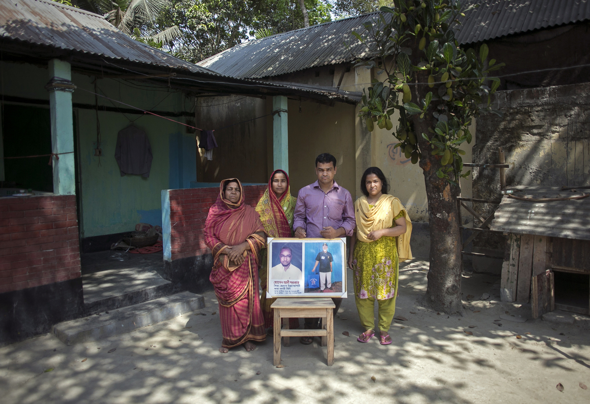 The wife and children (L-R Ambia Begum, Hasina Begum, Rahul Amin Azad, and Nasima Akhter) of Christian convert Hossain Ali, who was murdered by ISIS, hold his photograph as they pose for a photo in Kurigram, Bangladesh. On March 22 Ali was taking his usual morning walk when he was attacked and died. Ali was a Navy Commander during Bangladesh's 1971 Liberation War, and converted to Christianity 16 years ago. The police warned him and his family to be careful and limit their movement because of the ongoing security issues, but Ali felt safe since he said he had no enemies. ISIS claimed responsibility for his murder. He is remembered as a gentle, simple and happy man, and he leaves behind a wife, mother, and three children.