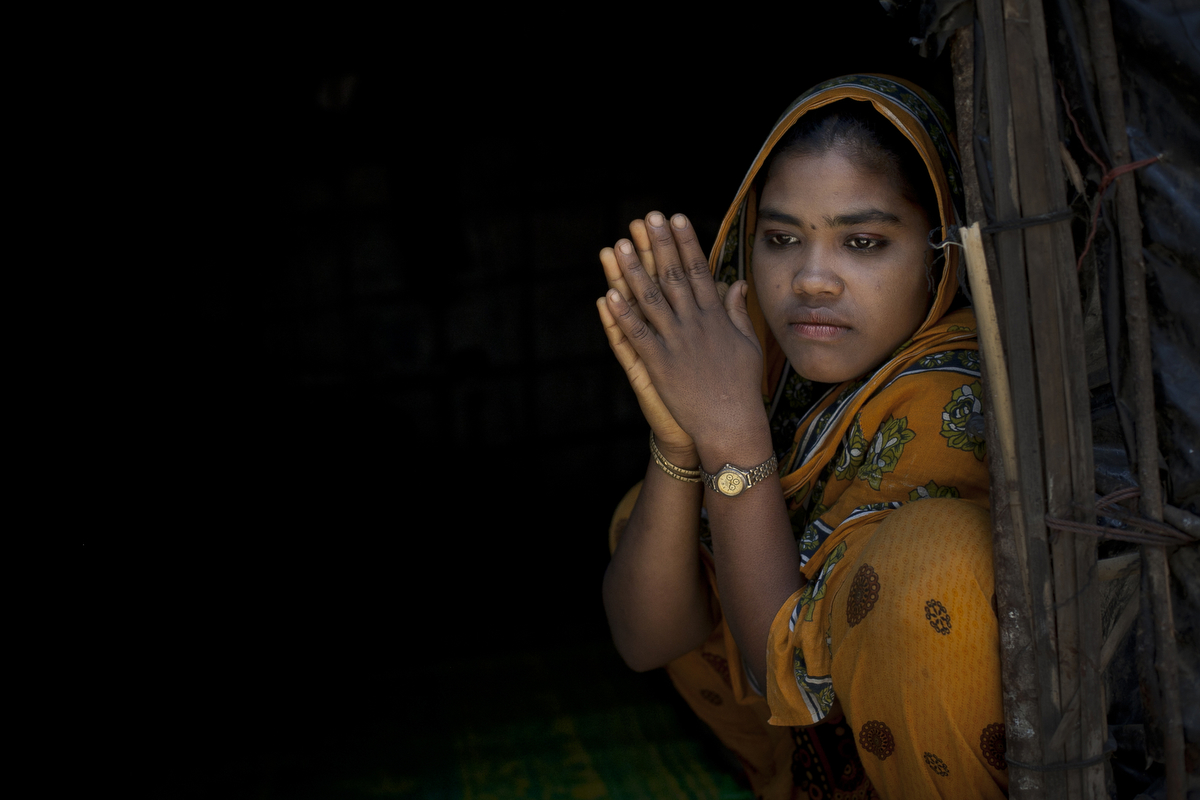 Rajama sits in the doorway of her home in the Shamalapur Rohingya refugee settlement in 2014 in Chittagong district, Bangladesh. She fled to Bangladesh 5 months ago from the Dhuachopara village in the Rachidhong district of Myanmar. The Chakma people came on a Friday during prayer time in a giant mob and started burning houses and burning people alive. They beat her father and brother, and then they opened fired and started shooting and killing people at random. A group of people fled to the mosque and the Chakma followed, opening fire inside. Her father fled to the ocean and escaped to Bangladesh by boat. Rajama came to Bangladesh 3 days after the riot to find her father. When she arrived in the port of Teknaf the dock workers held her captive for 3 days with no food or water. They beat her and abused her before letting her go. She has 7 siblings back in Myanmar who were not able to escape. {quote}I miss my family, but how can I miss them? I want to live.{quote} she says.