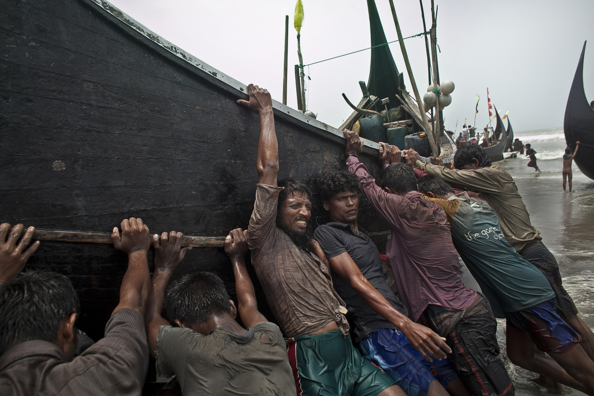 Rohingya men push a fishing boat to shore in 2015 in Shamlapur, Bangladesh