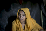 Fareza becomes emotional as she talks about being raped by the Myanmar military in her makeshift house that she shares with 6 other refugees in 2017 in Balu Kali Rohingya refugee camp in Cox's Bazar, Bangladesh. Fareza, 17, came to Bangladesh 3 days ago from Shilkhali village in Myanmar. She describes a happy life in Myanmar until 4 months ago when the military began attacking and harassing people in her village. Last Monday, January 16, 2017, she says that a group of soldiers attacked her home and dragged her and her family out into the front yard and beat them with their fists and the butt of their guns. They groped her everywhere and dragged her back into her house where one soldier raped her until she lost consciousness. She woke up bleeding and decided to flee to Bangladesh, where she made her way to Balu Kali refugee camp. She is 6 months pregnant and has not been able to make contact with her husband back in Myanmar. {quote}For 4 months back in Myanmar I lived in a constant state of fear. At least here in Bangladesh I can sleep peacefully.{quote}