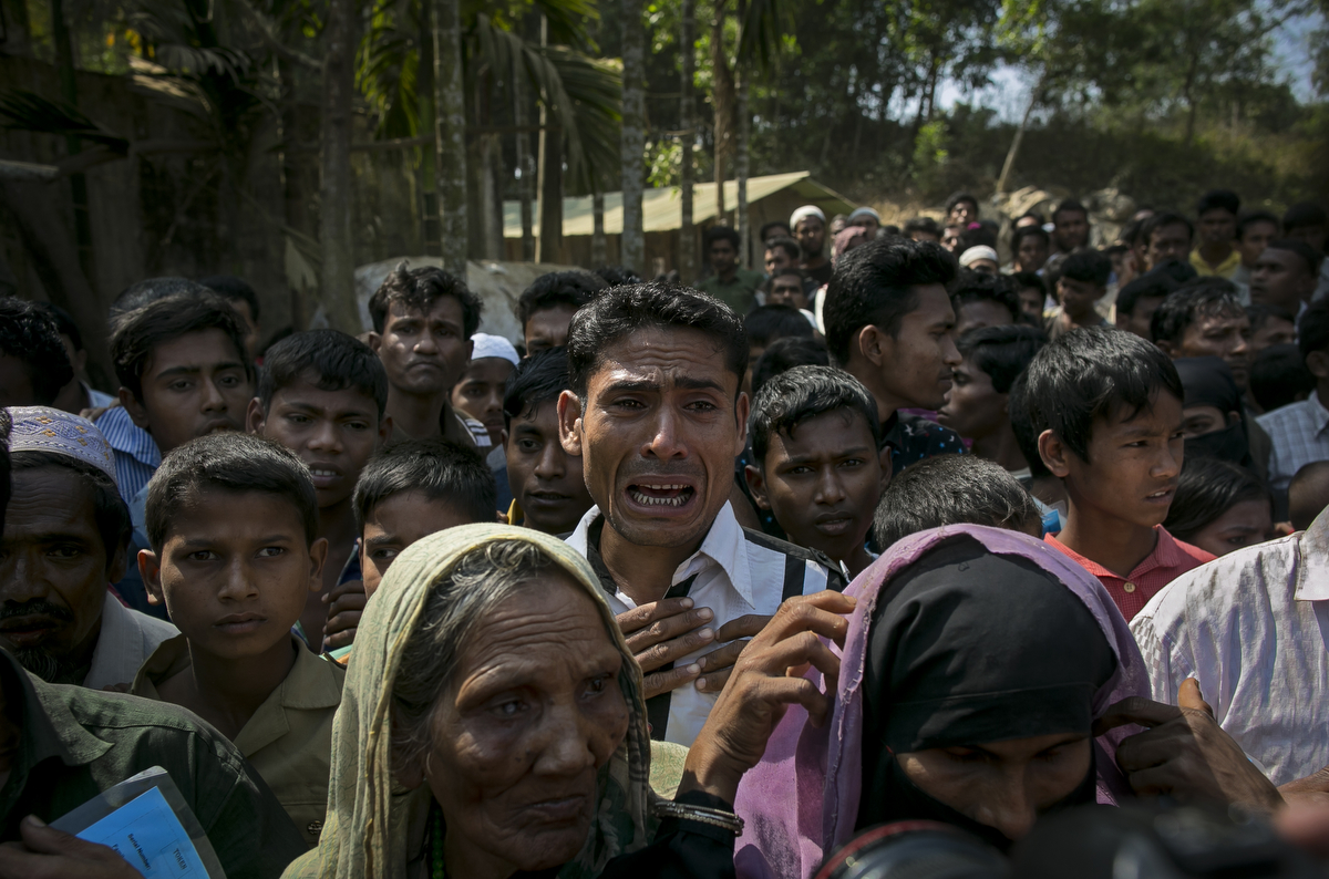 A refugee cries as a limited number of relief supplies are donated in the Kutupalong camp
