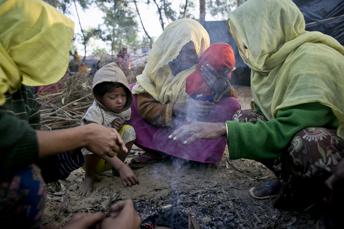 Families huddle around a fire early morning in the Balu Kali refugee camp in 2017