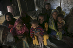 A group of women sit on the floor of their home in Balu Kali refugee camp is seen in 2017 in Cox's Bazar, Bangladesh. They are all relatives and came from the Naine Chong Village in Myanmar. They escaped to Bangladesh 1 week ago after the Myanmar military attacked their village. They escaped and hid in the hills for 7 days before they were able to escape to Bangladesh. They each had to pay 30,000 Myanmar Kyat (about $22) to a boatman smuggler to take them across the Naf river to Bangladesh. 17 people share this house but, {quote}At least here we can sleep in peace{quote}, they said.