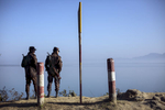 Border guards stand near the edge of the Naf river which separates Myanmar from Bangladesh