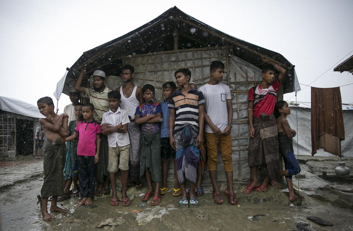 Rohingya are seen during a rainstorm at Nayapara refugee camp