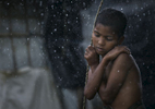 Rohingya are seen during a rainstorm at Nayapara refugee camp