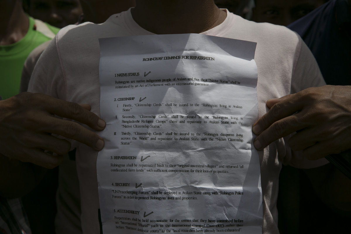 A Rohingya refugee displays a list of demands about Rohingya repatriation at Nayapara camp