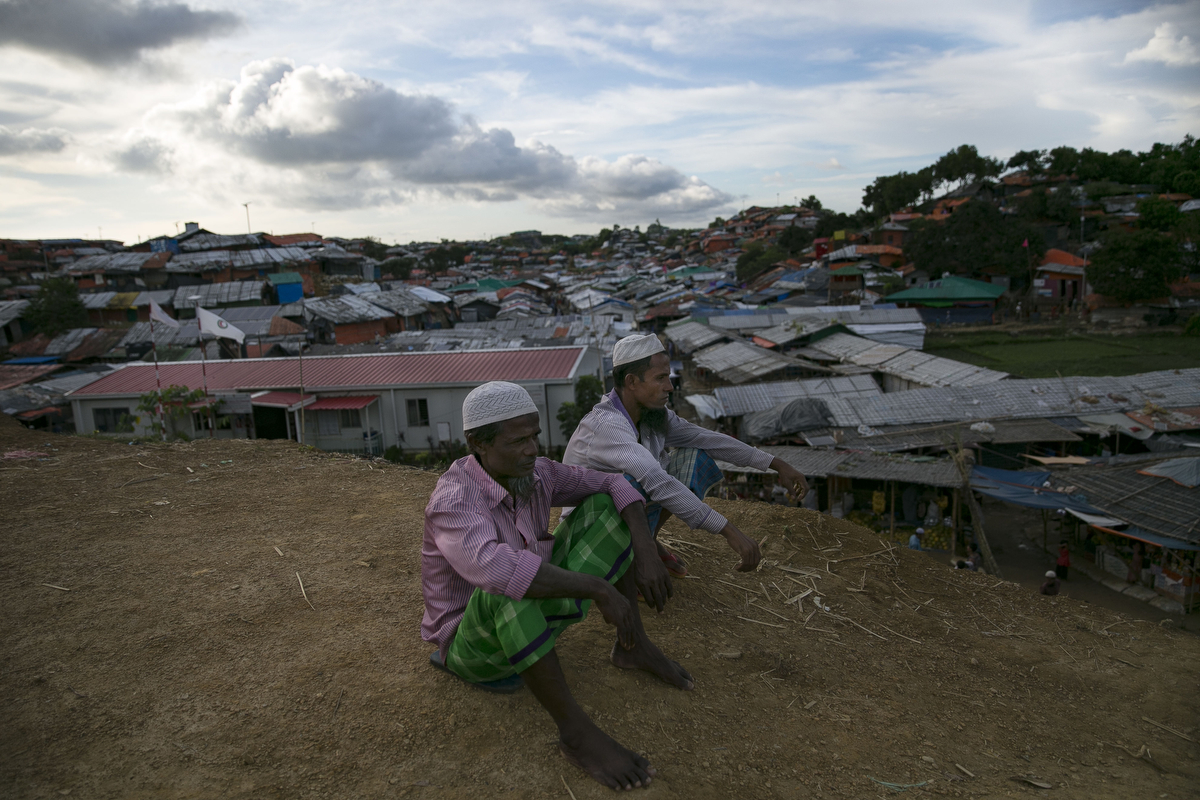 Men sit on a hill at a Rohingya refugee camp