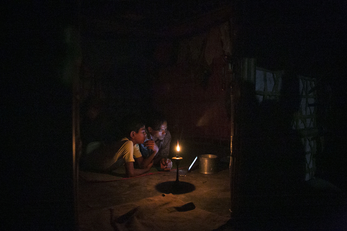 Children watch a video on a mobile in a Rohingya refugee camp