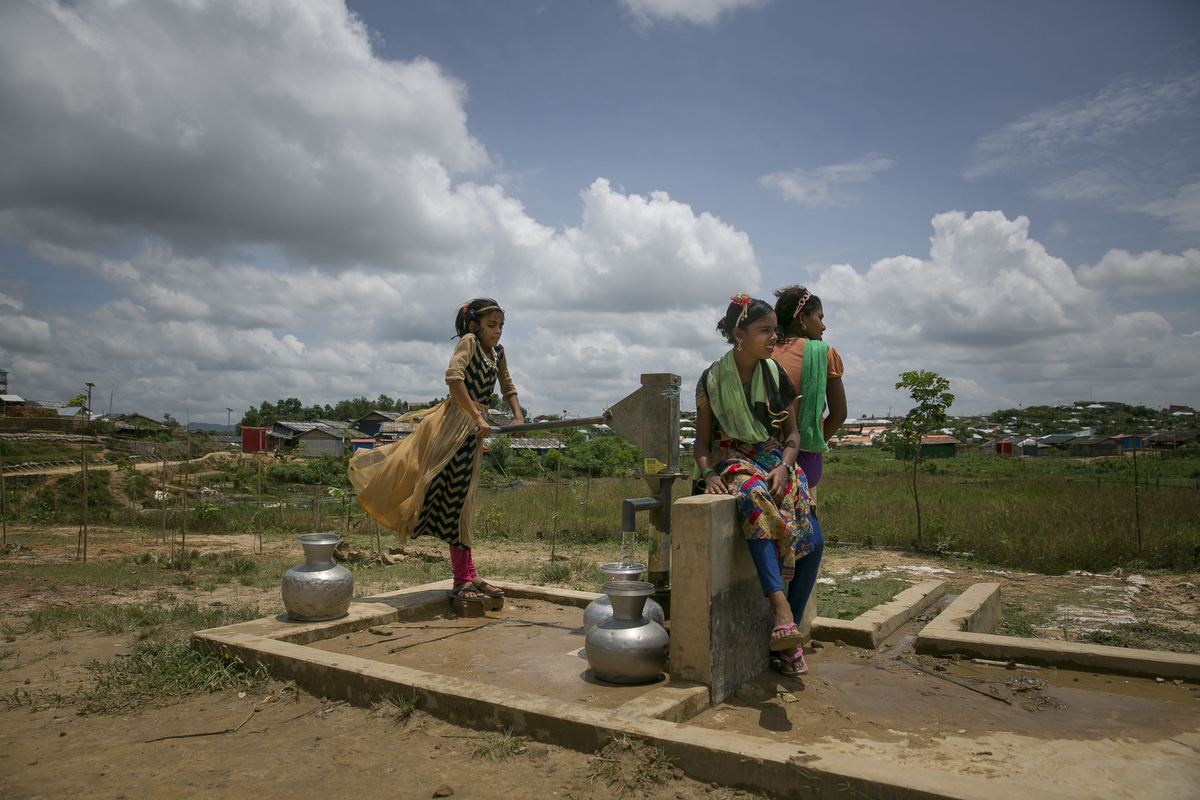 Girls pump water from a well in the camp