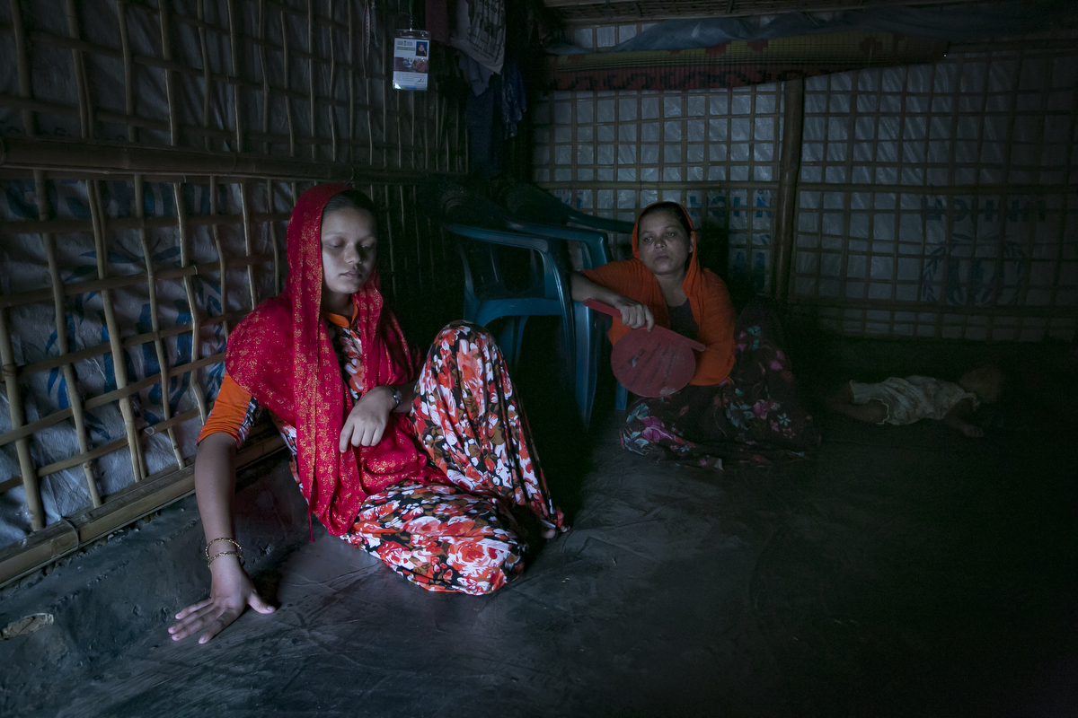 NurNahar Begum  and Yasmin are seen in their shelter. Yasmin Akhter, is a 14 year old wife and mother. She came to Bangladesh when she was 8 years old. She never had the chance to go to school. Her father left the family and left her mother, 40 old NurNahar Begum, and two years after she fled from Myanmar to Bangladesh she was sent to Chittagong to work as a housekeeper for a family of 5. She worked there for two years, never receiving a formal salary, getting only 200 or 300 taka occasionally. The mother that she worked for beat her frequently. She wasn't allowed to go outside, but Yasmin stayed thinking that it was the only way she could help her family.  One day she couldn't take any more and she called her mother and told her about the abuse, and said if she stayed there one more day she would die. Her mother brought her back to the refugee camp and arranged for her to get married. Yasmin was 12 years old when she married her 30 year old husband. When Yasmin was married she was happy, she thought that her husband would provide a better life for her, but he is sick and unable to work, and their food rations from the NGOs are not enough. 9 months ago Yasmin gave birth to a baby girl. She dreams of a better life for her daughter, one where she is independent, educated, and works a respected job. {quote}It will be up to her when she gets married{quote} Yasmin says. NurNahar Begum says {quote}I didn't have any choice, that's why I had to make this decision. I took two wrong decisions for her life. The first one sending her to Chittagong to work as a maid and the second one in getting her married. I didn't know it would turn out like this. I always tried to give my kids a good life but I failed. We never had enough food, no good shelter, they were never able to get an education. I failed.{quote}