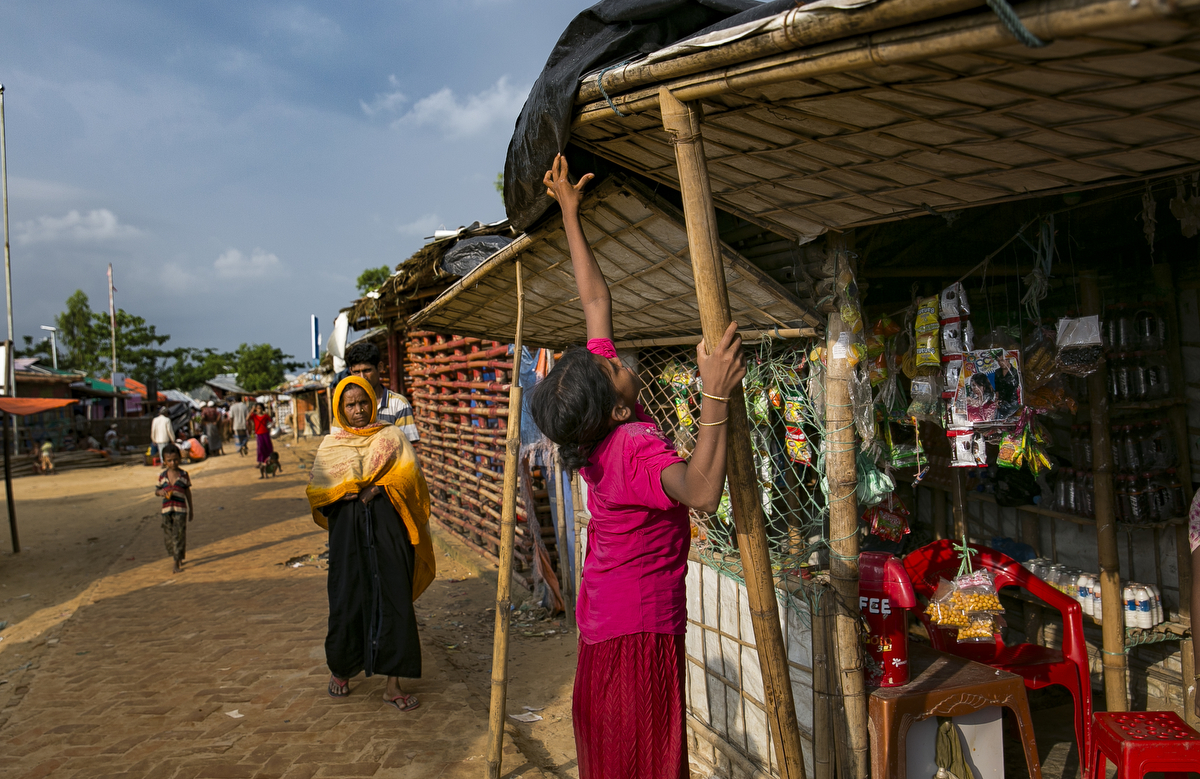 """12 year old Nur Kalima runs her mothers shop.Dildar Begum, 25, and her daughter Nur Kalima, 12 run a shop in Hakimpara camp. Her husband and other children were brutally killed in Myanmar. The money to open the shop was donated by a journalist who visited her. {quote}I'm better than before but inside my heart there lies so much pain. The extra money helps buy them vegetables and fish. Her daughter goes to the madrassa in the morning and runs the shop in the afternoons. {quote}I feel shy to be in front of other people. People will say I'm doing bad things. In our community women can't be outside and in front of people. My daughter runs this shop.{quote} After her daughter gets older and married she wont let her run the shop. She plans to just do sewing then. {quote}I have lost all my kids and my husband. In my mind there is no peace. This is Bangladesh, not my own country. We are provided with the things we need but it feels like nothing because this is not our own country. If we are given our rights we will go back, we can have a peaceful live. There is a lot of sadness in my heart. If Allah killed me I would be happy. I've seen a lot of people killed and I've been suffering here a lot."""" Her daughter Nur Kalima would rather be in school {quote}I can take an education anywhere I go. I cant take this shop anywhere.' — Dildar fled to Bangladesh shortly after the August 25th attack from Tula Toli village in Myanmar. She says that one day the military came and opened fired on her village and stormed into her house. They took her husband out of the house and to the riverbank and shot him. Then they came back into her house and grabbed her baby from her arms and stabbed him in the head. They killed another one of her children by cutting his throat, and another by beating her over the head with a rifle. 2 military held her arms while another raped her. They then beat her and she pretended to be dead. When they left, they set her house on fire. Her 10 year old daughter, Nurk"""