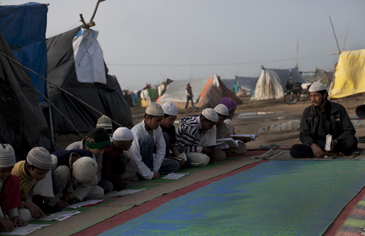 Children attend a makeshift Islamic school in the Barnavi relief camp.