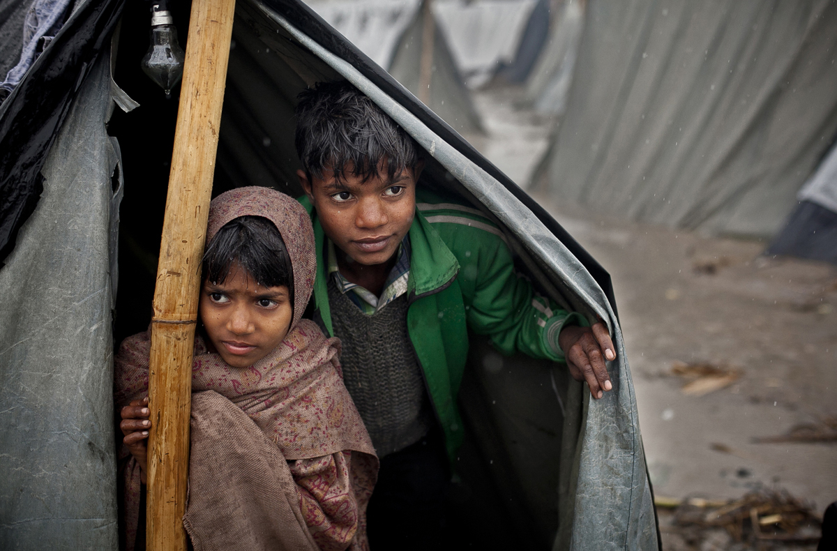 Young children look out of their tent during a rainstorm in the Jhola relief camp.