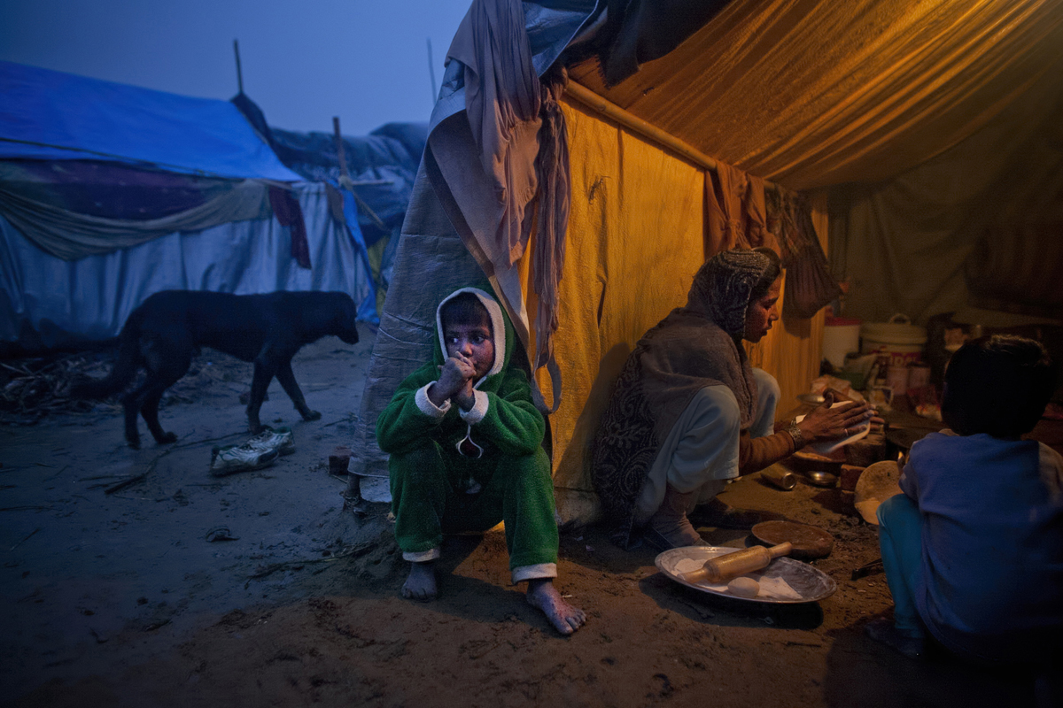 A child sits outside his tent while his mother cooks in the Malakpur relief camp.