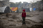 A boy stands in the rain in the Jhola relief camp.