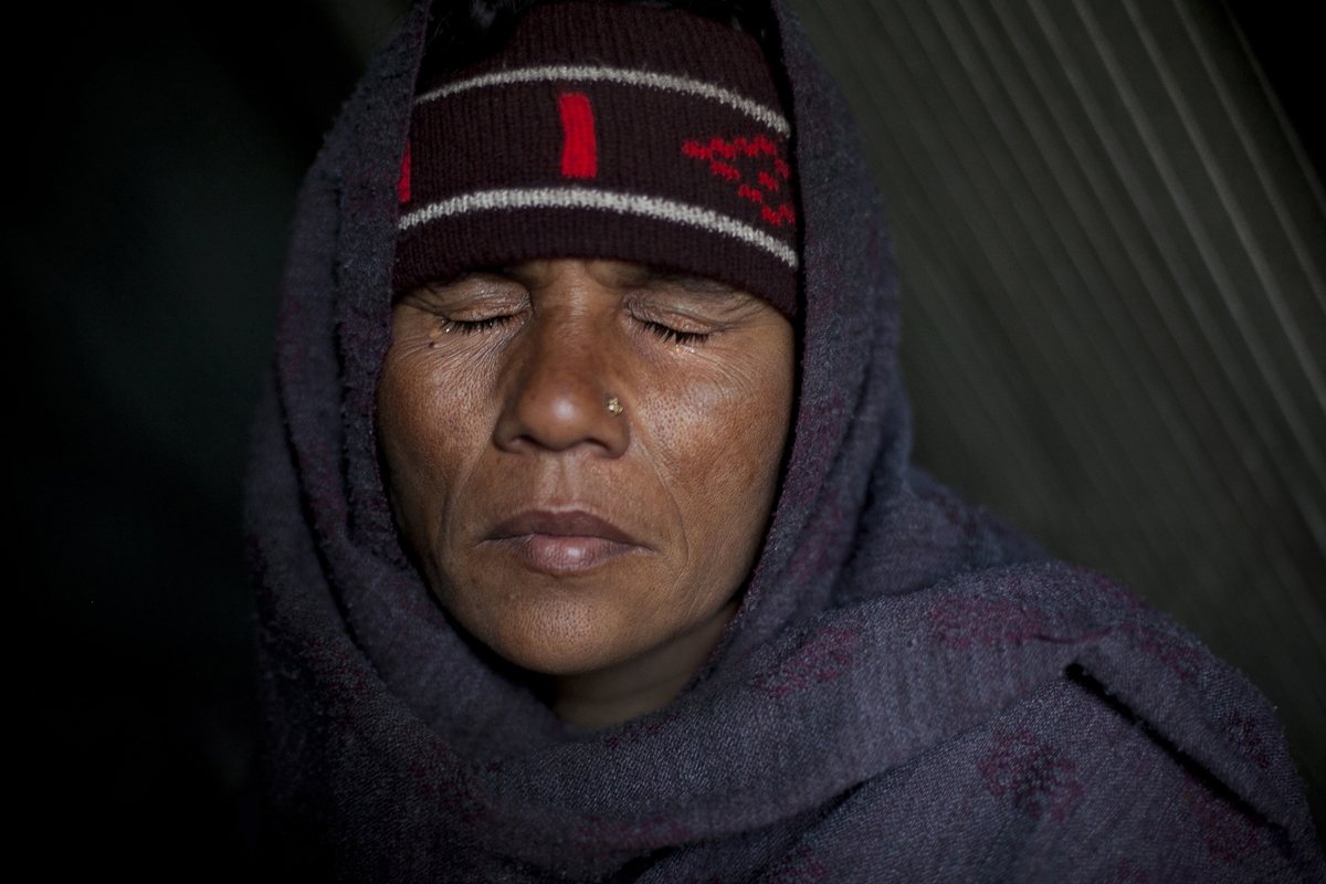 35 year old Akhatri Begum shuts her eyes against tears in the Jhola relief camp. She hasn't seen her husband since he fled their home during the riots. After the riots she suffered a miscarriage, and she has been living in a small tent at the camp with her two children for 5 months.