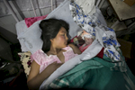 Enora Warmalai lays next to her newborn daughter in the maternity ward of a hospital