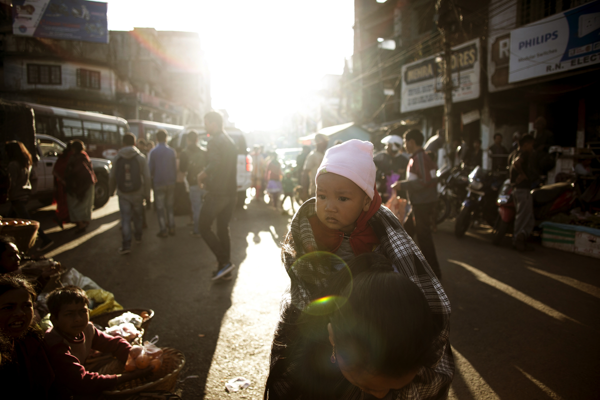A woman shops with a baby on her back at a market in Shillong