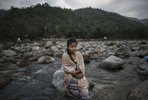 A girl sits on a rock in Shnongpdeng Village