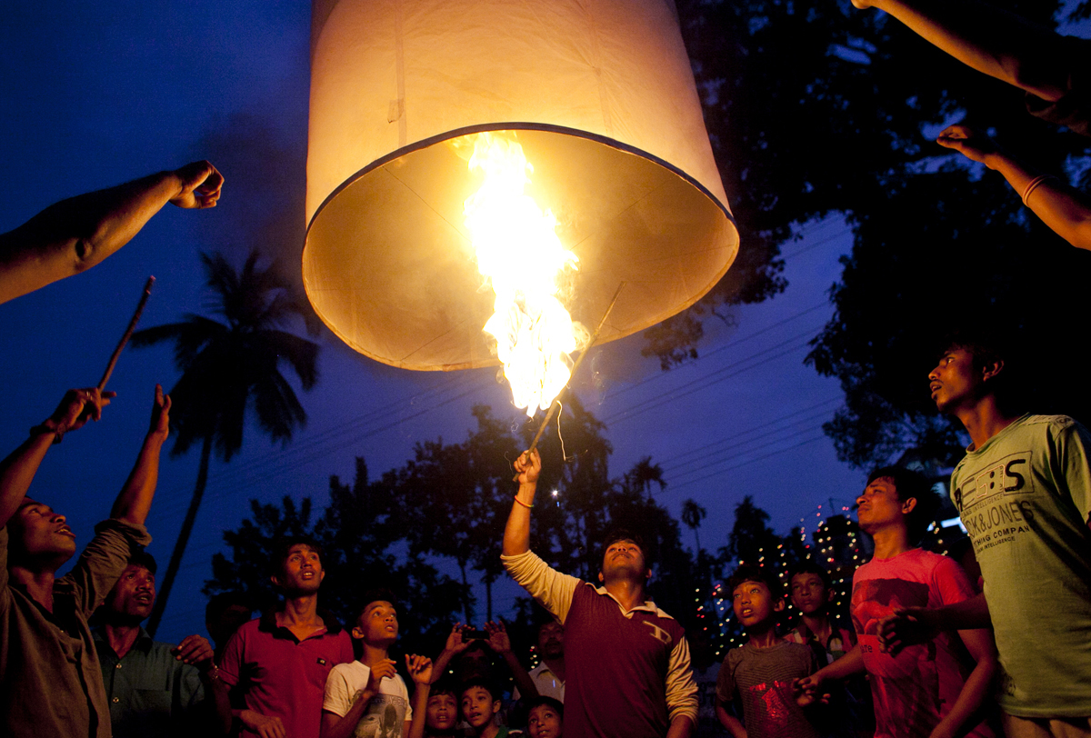 Bangladeshi Buddhists light a large paper balloon into the sky during Probarona Purnima in Ramu, Bangladesh. The Probarona Purnima festival celebrates the conclusion of the three-month long seclusion of the monks inside their monasteries for self-edification. Last year, on September 29th 2012 a muslim mob attacked and destroyed temples and homes of Buddhists after an anonymous person posted a photograph of a desecrated Quran on a local Buddhist boy's facebook wall. The community did not participate in Probarona Purnima last year in protest of the attacks.