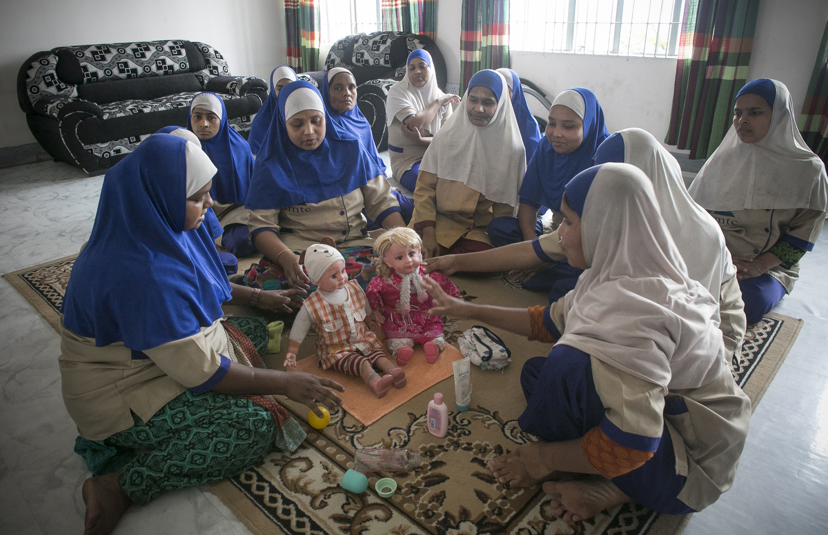 Women train at a school as nannies and domestic workers before going for a job posting overseas, at a school in Dhaka, Bangladesh.
