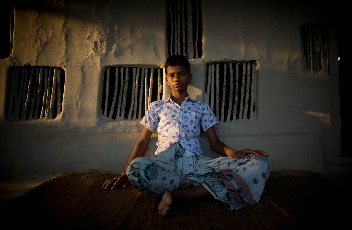 "Rahul Morol, 14, is photographed outside his home one year after being attacked by a tiger while fishing with his cousin. ""After the attack it took one and a half months to fully recover. Before the attack I was not afraid of tigers, but now I feel afraid.{quote} Rahul no longer works and has vowed never to return to the jungle. When his father ventures into the jungle, he fears for his safety, remembering the horror of the tiger attack. His cousin, too frightened to continue living and working in Jotinronaghor, left Bangladesh after the attack and now works as a painter in India.  Ruhel plans to be a shrimp farmer in the future and says, ""I have no other plan. No other option."""