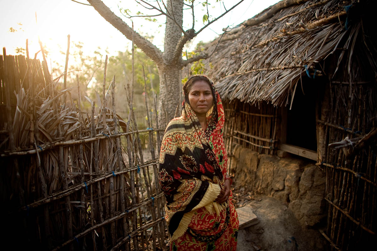 "Kushum Mondul stands outside her goat house in the town of Golakali. ""I was inside my house at the time. When the tiger entered the goat house next door it broke through the wall. I was sitting on my bed and I called for my older sister. I told her that I heard the goats being killed by the tiger. We were trying to think what we could do. My older sister was so scared; she lost control of her bladder. We started screaming inside the house; some villagers heard and they came. My sister said to stay inside, if you open the door we might be in danger. We tried to scare the tiger off by hitting a large plastic container, hoping to make enough noise to scare off the tiger, but he killed 9 goats. The villagers came yelling, pushed the tiger away, and they killed it. I cried for the loss of my goats. Now I have to fish in the river. At sunset I start to get scared thinking the tiger will come again, and I lock my door.  We don't leave our home at night; we keep a pot inside the home for bathroom use. I'm a poor woman. I made my living by raising goats, but the tiger killed all my goats. What am I to do now?"""