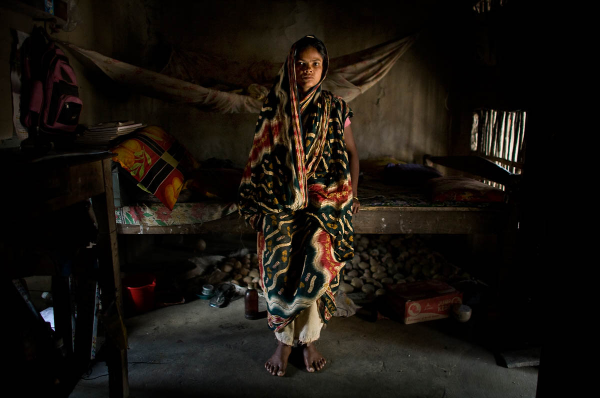 "Ali Moti is photographed in her home in Moturapur.  She doesn't know how old she is, but guesses she is 25. Her husband, Nabo Kumar Mandol, was killed by a tiger last year while he was fishing in the Purakalla canal. Ali was cooking in her neighbor's house when she was told about the attack. ""When I heard this I was senseless, crying.  I had to be carried home and was unconscious about 30 minutes. The forest response team took my husband's body back to this town; I fainted again when I saw it.""  Ali must work to support herself and her two children, as well as a brother and sister-in-law. She now has a job repairing the roads in her town and earns 1,500 taka (about 14 usd) per week. Her brother-in-law is too afraid to work in the jungle.  He works on the mainland, and jobs are scarce; although he looks for work every day, he has not managed to find more than two days' work each week. Her son catches crabs close to the mainland, not in the forest, making only 20-50 taka (18 to 46 cents) per day. ""I was 15 when my mother and father told me I was going to be married. I didn't want to leave my parents and live with a man I didn't know, so I tried to run away.  My husband and I had a good marriage and a good life. He loved me and I was fortunate because my sister- in- law and I became very good friends. She will be married soon. I don't miss my husband; I can survive by myself and take care of my son and daughter. Things are okay but sometimes I have to borrow money. Things are not good, but okay."""