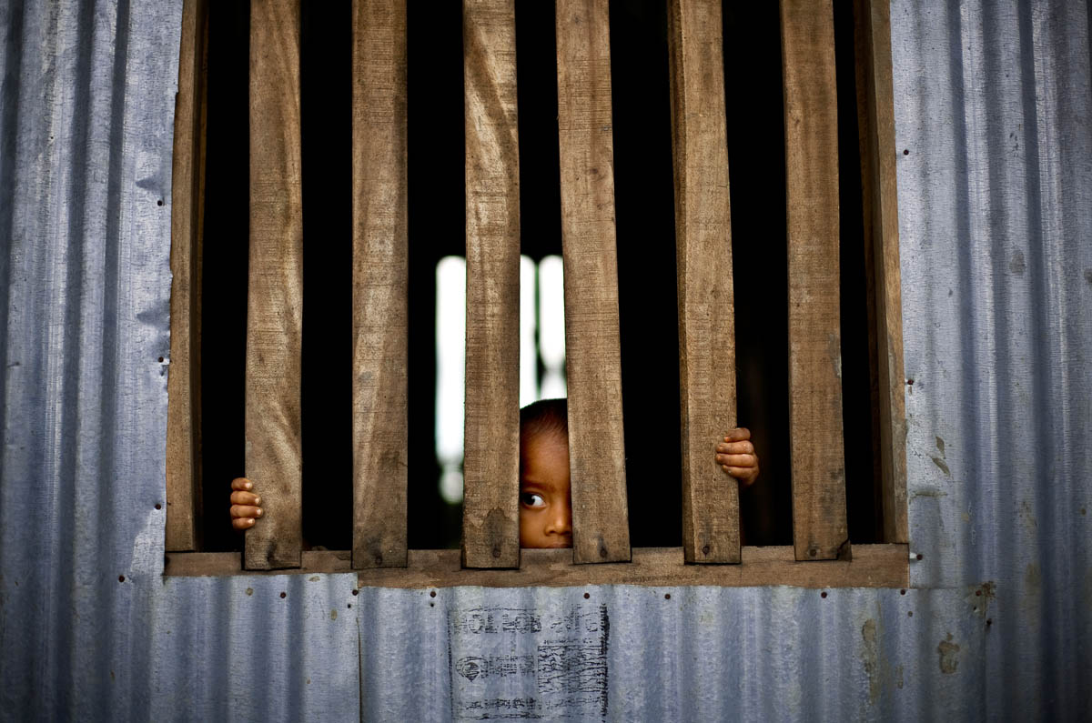 A boy peers through the bars of his home in the Sunderbans
