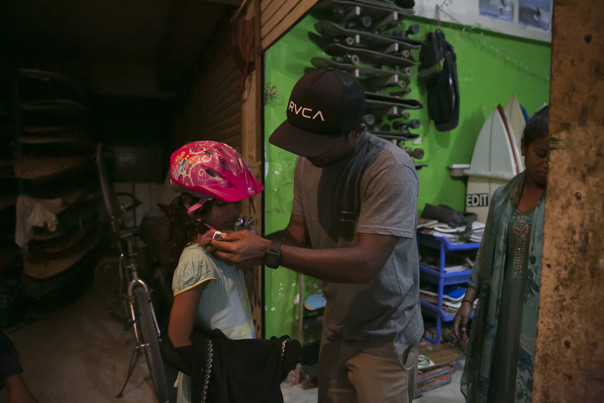 Rashed adjusts the helmet of a new surfer girl before skateboarding
