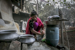 Soma washes dishes outside her house
