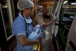 A newborn baby is transferred into an ambulance at the Akanksha IVF center.