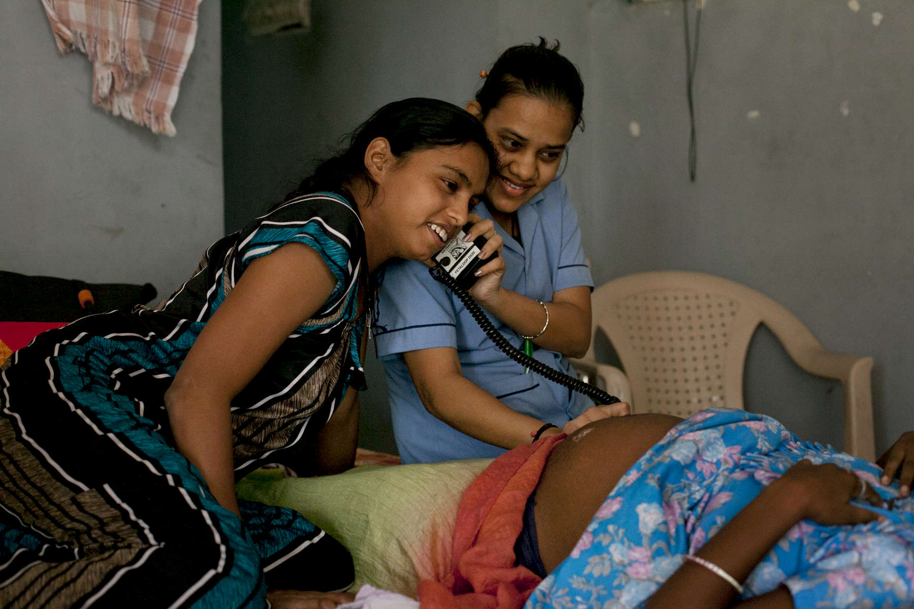 A nurse and a surrogate mother listen to a baby's heartbeat in a dormitory run by Akanksha Clinic, one of the most organized clinics in the surrogacy business. The dormitory in Anand, houses scores of young women, all hired as surrogates for foreign couples.