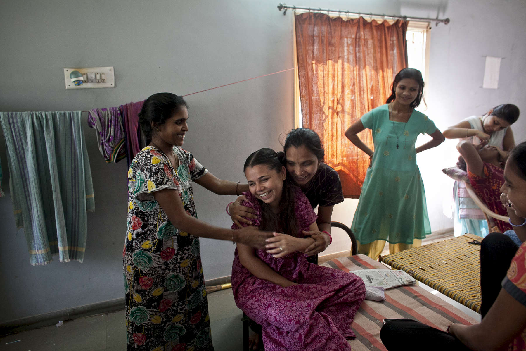 26-year-old Christina Christian, center left, socializes with other surrogate mothers at a dormitory run by Akanksha Clinic, one of the most organized clinics in the surrogacy business. Christian is carrying a child for American parents and says she plans to use the money she earns to purchase a house. The dormitory in Anand, houses scores of young women, all hired as surrogates for foreign couples.