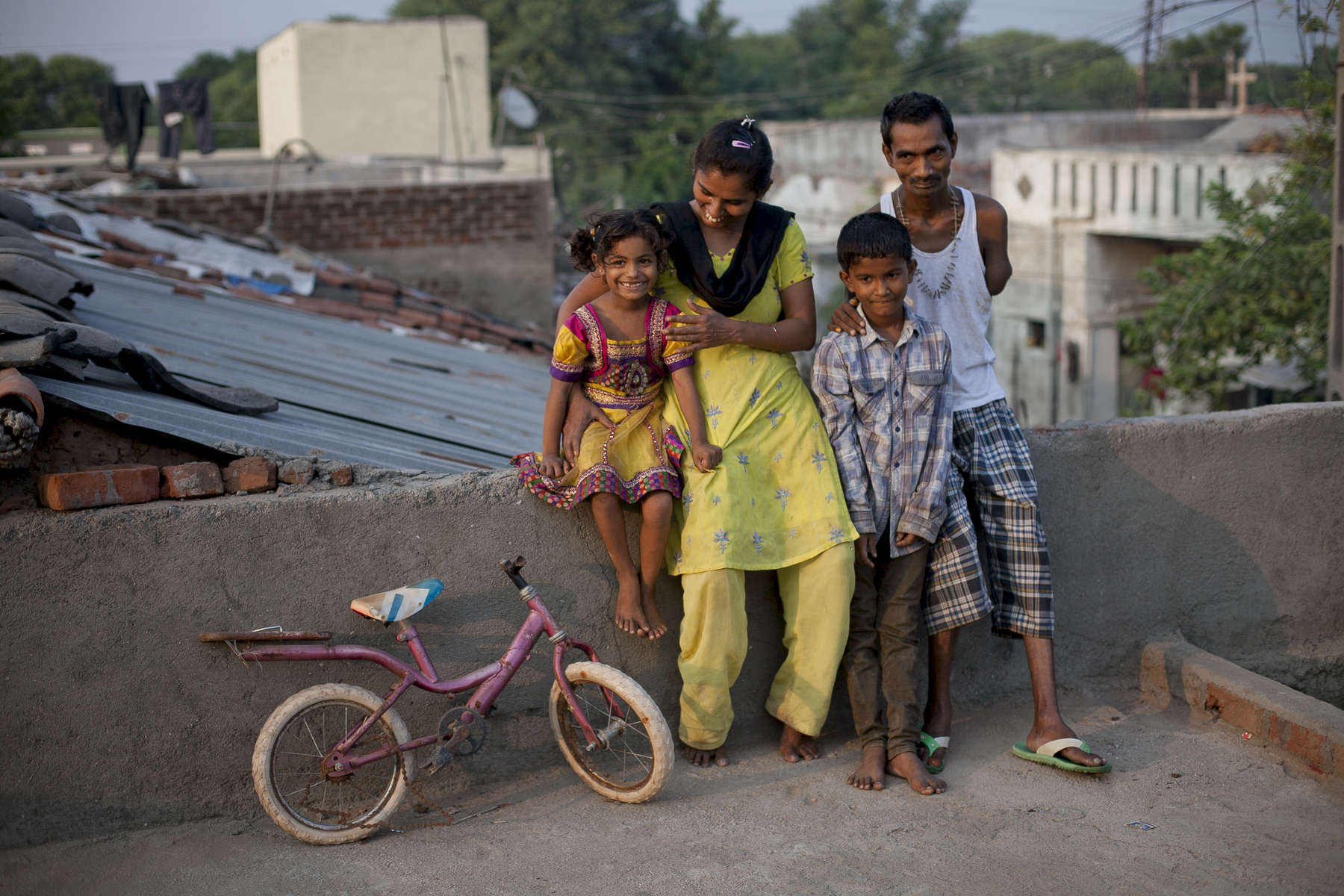 Two time former surrogate mother Kokila Mecwan stands for a photograph with her husband and kids on the roof of their home. Kokila was a surrogate for parents from the UK and Canada. With the money she earned she was able to take care of her husband's medical expenses after he lost his arm in a train accident, build a roof with a terrace for her home, build a toilet and kitchen, send her children to private boarding schools, and more.