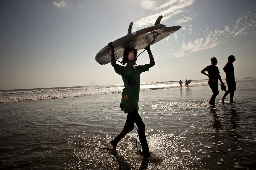 Johanara walks with her board during the annual surf competition