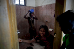 The girls rinse off in a washroom after surfing