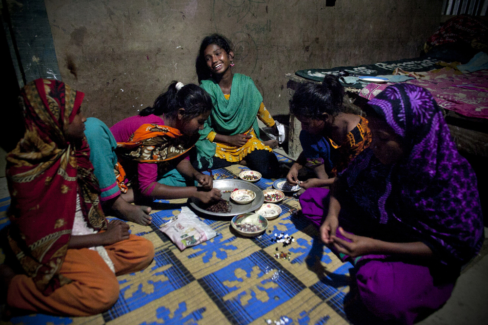 12 year old Maisha laughs in her home as she and the girls make jewelry to sell on the beach in Cox's Bazar, Bangladesh.