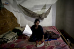 Sumi, the only girl who is able to go to a formal school, does homework on ther bed
