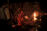 Johanara stokes a cooking fire in her home