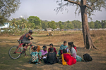Rashed looks on as his wife Venessa tutors the girls in a park near the beach
