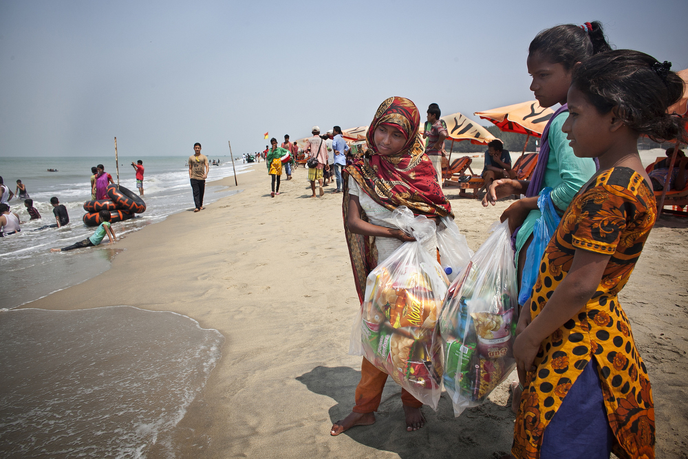 Johanara, Suma and Aisha sells items on the beach